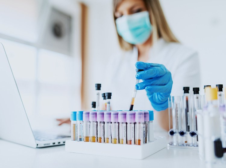 Female lab technician analyzing urine samples for drugs.