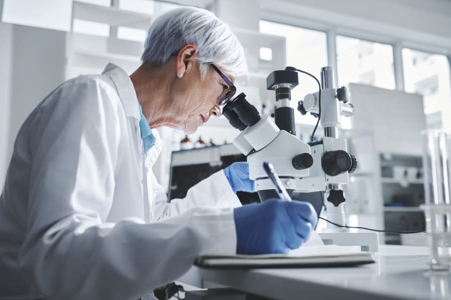 Lab expert analyzes sample under microscope
