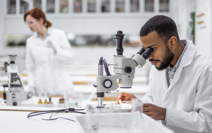 Lab technician analyzing sample under microscope